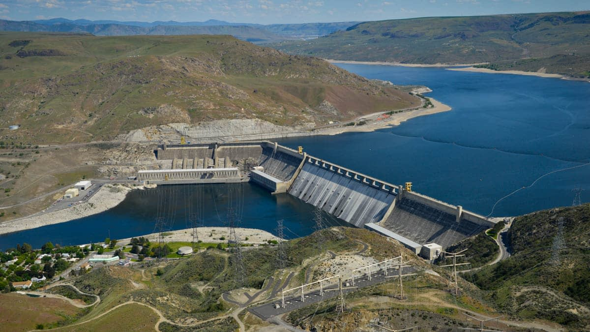 Aerials of Grand Coulee Dam. Take note of the newer materials storage building downstream of the third powerplant. A tempora
